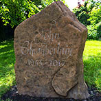 Script font hand engraving on rock headstone