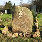 Sarsen stone headstone with hand carved sun symbol and inscription