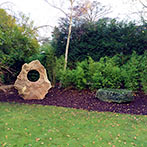 Sarsen stone holed stone and Cornish glacial granite seat stone in London twon garden