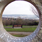 Glacial granite holed stone with memorial inscription within the hole framing view of the Medway river and Rochester in the distance