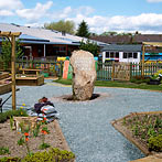 Standing boulder lends a strong sense of place to a primary school gardening area